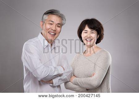 Happy Asian middle-aged couple studio portrait shot