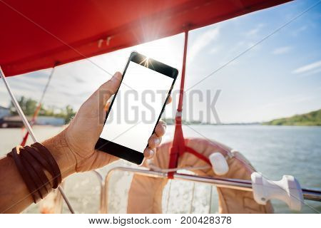 Summer rest. Relax on a yacht with a phone in hand. A man lying on the deck and enjoying your smartphone. The guy takes a photo of his feet against the background of the river landscape and yachts.