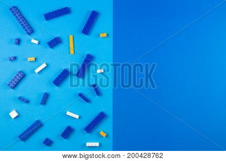 Toys background. Top view of plastic construction blocks on blue background