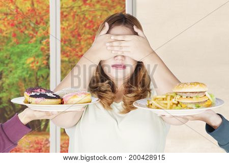 Obese woman reject to eat junk food with closing her eyes autumn background on the window