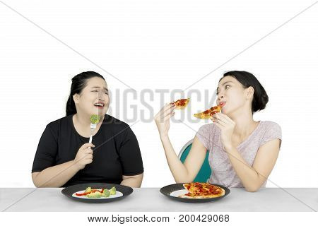 Diet concept. Overweight young woman eating salad and looks envy looking at her friend eating pizza