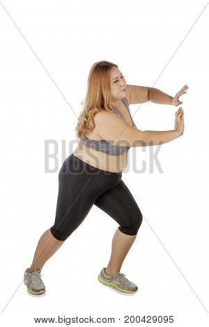 Overweight woman with blonde hair wearing sportswear and pushing something in the studio