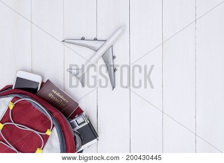 Airplane flying off traveler backpack on white wood copy space