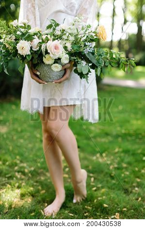 beauty, appearance, nature concept. charming sylphelike creature with long thin legs wearing white dress with lace cloak holding vase with large gorgeous bouquet of flowers