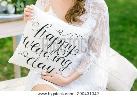 comfort, holiday, celebration concept. young fair-haired woman wearing radiant lace cloak on her shoulders keeping small cushion with words printed in italic style
