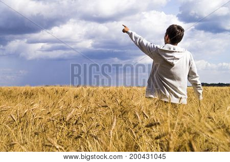 Man In A Wheat Field Showing His Fingers In The Direction Of The Sky