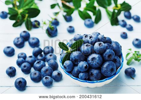 Blueberry or great bilberry in bowl on blue vintage table. Organic superfood and healthy nutrition.