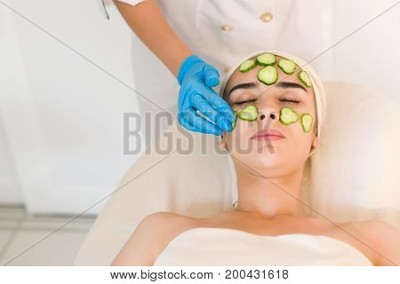 Young woman with facial mask of cucumber in beauty salon. Cosmetic mask is applied to the face of a woman.