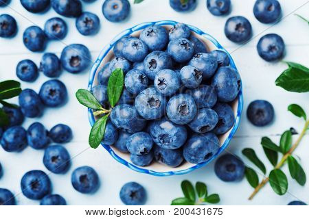 Blueberry or great bilberry in bowl on blue wooden background top view. Organic superfood and healthy nutrition.