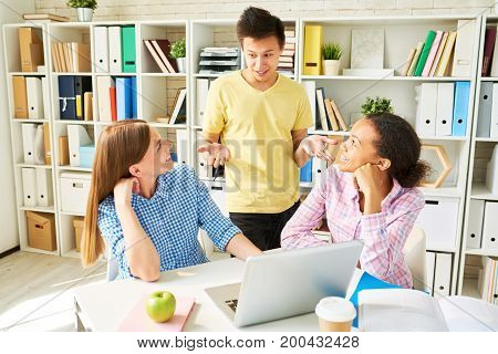 Portrait of three students studying together  in library Asian man explaining something to friends