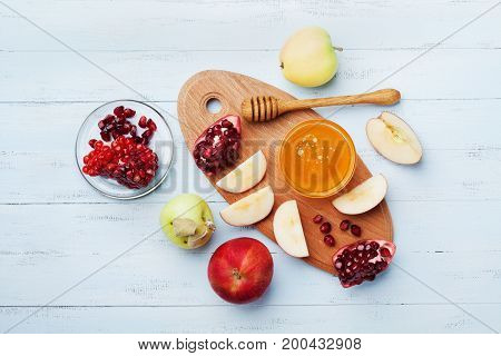 Honey apple slices and pomegranate serve on kitchen board top view. Table set with traditional food for Jewish New Year Holiday Rosh Hashana.