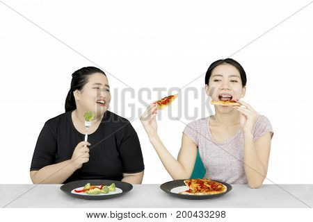 Diet concept. Overweight woman looks envy looking at her friend eating pizza while eating salad