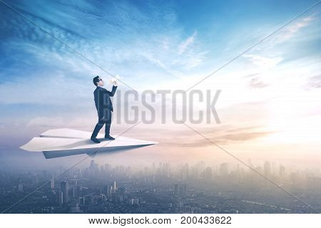 Male worker flying on a paper aeroplane and shouting with a megaphone above a city at sunrise time