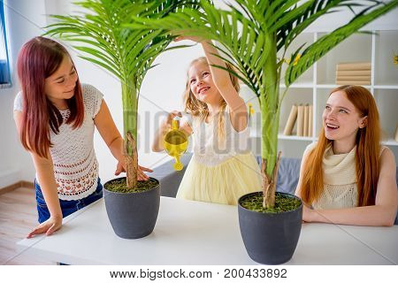 Mom with two daughters watering plants in pots