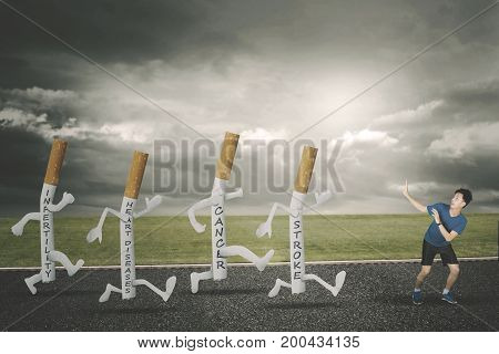 Image of young man looks afraid while chased diseases of four cigarettes