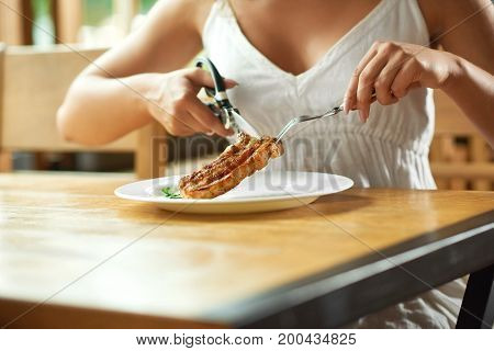 Cropped shot of a woman having grilled steak at the restaurant cutting it with scissors eating food lunch hunger hungry cafe diner concept.