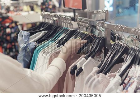 Female Hands Rummaging In Clothes In A Second Hand Shop