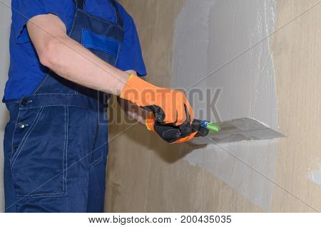 Plastering shpatlyuet wall with a spatula and white putty