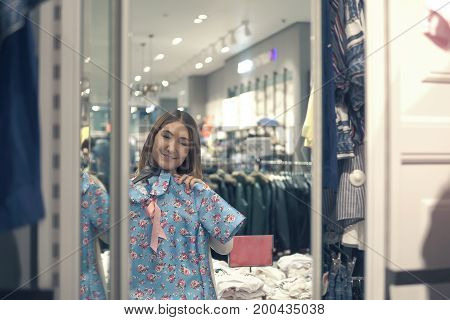 Happy Asian Woman Choosing Clothes And Looking To Mirror In Mall Or Clothing Store