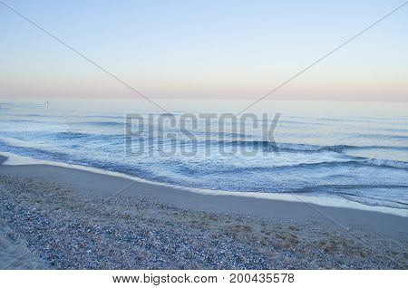 Summer evening at the seashore. View of the soft sea wave on the sandy beach.
