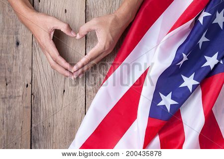 Gesture made by hands showing symbol of heart with american flag on old wooden background