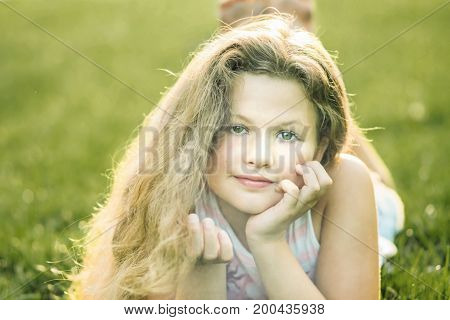 A teenage girl touching long hair and lying on grass in summer