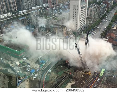 WUHAN, CHINA - AUGUST 17 2017: dust cloud spreading in city street after a building collapse during demolition