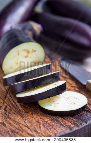 Preparing vegetable dish. Eggplant and eggplant slices on wooden cutting board and background vertical