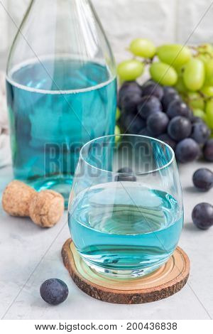 Trendy blue moscato wine in a glass and in bottle green and red grape on background vertical