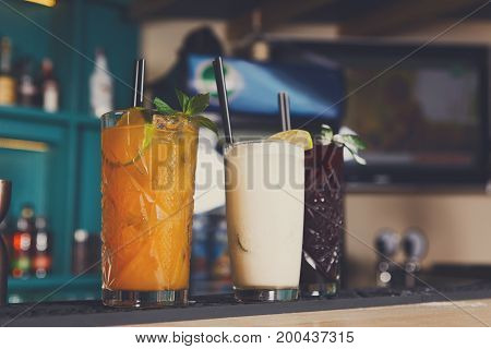 Creative sweet exotic alcohol cocktails at bar background, three glasses on table, refreshing drinks with straws.