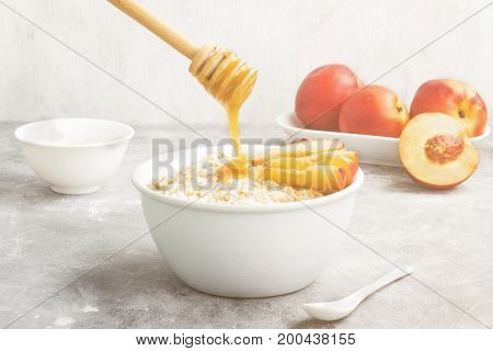 Oatmeal With Nectarine And Honey On A Gray Background. Toning
