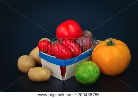 Assortment organic vegetable colorful tomatoes and potatoes on black background