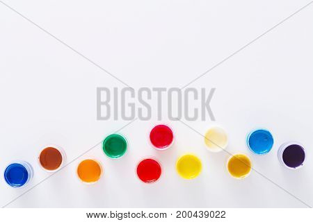 Color gouache jars on white background, isolated, top view, copy space