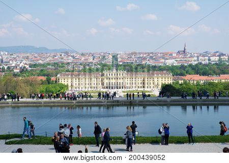 VIENNA, AUSTRIA - APR 30th, 2017: Classic view of famous Schonbrunn Palace with Great Parterre garden with people walking on a sunny day with blue sky and clouds in summer. The palace is a former imperial 1441-room Rococo summer residence of Sissi Empress
