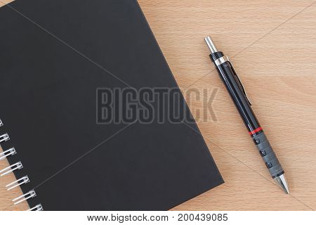 workspace on wood table with notebook and pen. copy space