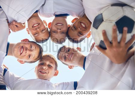 Low angle portrait of junior football team standing in circle, huddling and smiling  at camera against blue sky
