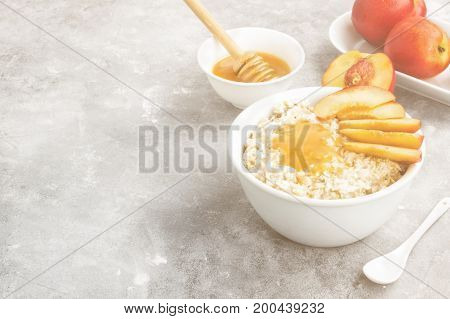 Oatmeal With Nectarine And Honey On A Gray Background. Copy Space. Food Background. Toning