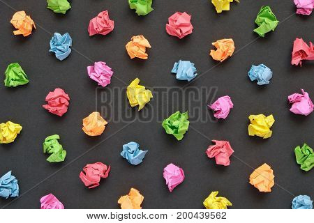 Colorful crumpled papers on black paper background