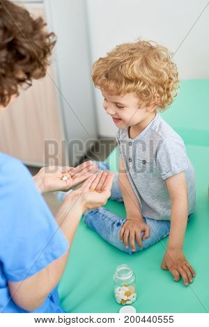 Back view portrait of young nurse giving pills and vitamins to adorable little boy enjoying checkup at doctors office