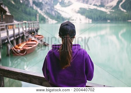 Woman in nature. Lake in a wilderness nature. Braies lake in a italian dolomites. Sunrise in nature. Background. Wooden hut. Beautiful summer view