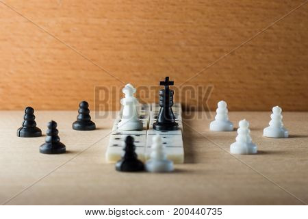 The chess king and the queen with their servants pawns stand on a carpet laid out of dominoes on a wooden background