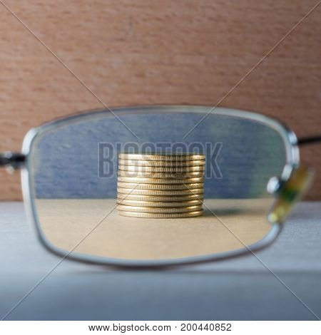 pile of gold coins is shiny and bright through eye glasses on a wooden background