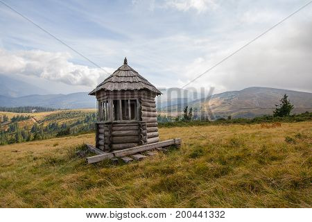 Old wooden lodge in the background of the mountains. Carpathians