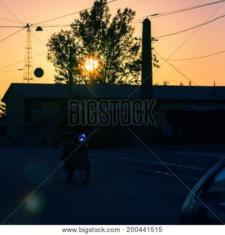 motorcyclist rides along the road at sunset lighting his way with a lantern