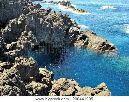 Rugged coast with a rock arch and very blue sea, Madeira