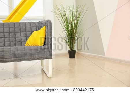 Interior of light modern room with sofa and floral decor