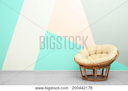 Comfortable rattan lounge chair in room near color wall