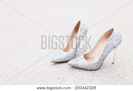 Shining silver high-heeled footwear shoe standing on the road