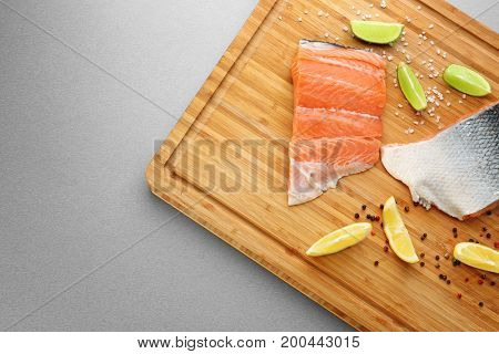 Fresh salmon fillet with spices and citrus fruits on wooden board