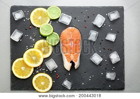 Fresh salmon steak with spices, citrus fruits and ice cubes on slate plate
